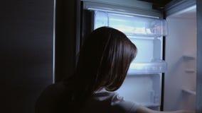 Ung kvinna på kylen på natten arkivfilmer