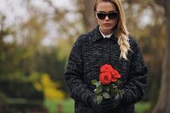 Ung kvinna på kyrkogården med nya rosor Arkivbild
