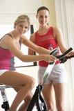 Ung kvinna på motionscykelen med instruktören Arkivbild