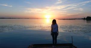 Ung kvinna på pir vid floden på solnedgången stock video