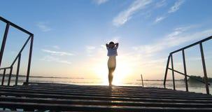 Ung kvinna på pir vid floden på solnedgången lager videofilmer