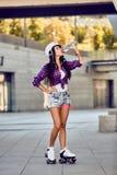 Ung kvinna på rullskridskor och hjälmdricksvatten royaltyfri bild