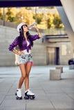 Ung kvinna på rullskridskor och hjälmdricksvatten Royaltyfri Fotografi