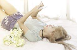 Ung kvinna på sängbruksmobiltelefonen royaltyfria foton