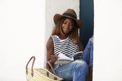 Ung kvinna på sammanträde på moment som läser upp en resehandbok, slut arkivbilder