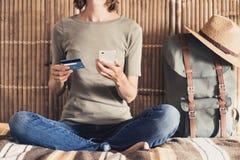 Ung kvinna på semestrar genom att använda smartphonen och kreditkorten Online-shopping- och loppbegrepp fotografering för bildbyråer