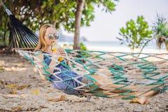 Ung kvinna på stranden i en hängmatta med en drink arkivbild