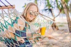 Ung kvinna på stranden i en hängmatta med en drink arkivfoton