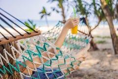 Ung kvinna på stranden i en hängmatta med en drink royaltyfria bilder