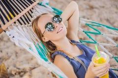 Ung kvinna på stranden i en hängmatta med en drink fotografering för bildbyråer