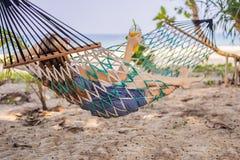 Ung kvinna på stranden i en hängmatta med en drink arkivbilder