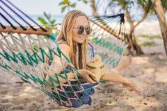 Ung kvinna på stranden i en hängmatta med en drink royaltyfria foton