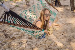 Ung kvinna på stranden i en hängmatta med en drink royaltyfri foto
