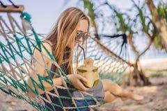 Ung kvinna på stranden i en hängmatta med en drink royaltyfri fotografi