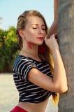 Ung kvinna på stranden nära ett träd royaltyfri bild