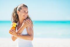 Ung kvinna på stranden som applicerar solkvarterkräm royaltyfri bild