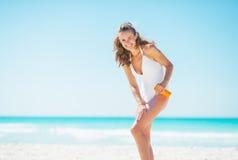 Ung kvinna på stranden som applicerar solkvarterkräm royaltyfria bilder