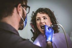 Ung kvinna på tandläkarekirurgi close upp royaltyfria foton