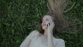 Ung kvinna på telefonsammanträde på gräset stock video