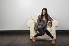 Ung kvinna p? en soffa arkivbilder