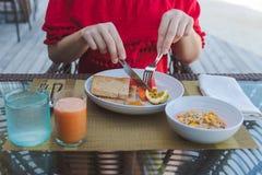Ung kvinna p? ferie i en tropisk ? som ?ter en sund frukost royaltyfri fotografi