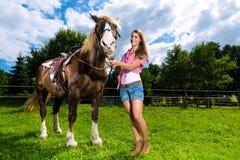 Ung kvinna på ängen med hästen Arkivbilder