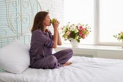 Ung kvinna på sängkanten i pyjamas som dricker te på backgren Arkivbild