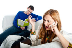 Ung kvinna som är chockad på något på telefonstunden som hennes pojkvän läser Arkivbilder