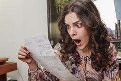 Ung kvinna som är chockad vid hennes räkningar Royaltyfria Foton