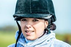 Ung kvinna som är klar att rida på hennes häst med hennes hjälm royaltyfri foto