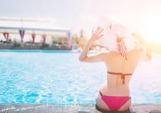 Ung kvinna som är lycklig i den stora hatten som kopplar av på simbassängen, lopp nära stranden i solnedgången begreppssommar arkivfoton