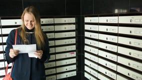 Ung kvinna som är lycklig med det mottagna brevet stock video