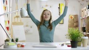 Ung kvinna som är lycklig, medan sitta vid tabellen lager videofilmer