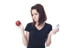 Ung kvinna som är sönderriven mellan en chokladstång och ett nytt äpple Arkivfoton