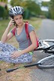 Ung kvinna som är stupad ner från cykeln som kallar för hjälp Royaltyfri Foto