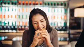 Ung kvinna som äter den fettiga hamburgaren Begärsnabbmat Tycka om skyldigt nöje som äter skräpmat Tillfredsställt uttryck avbrot royaltyfri fotografi