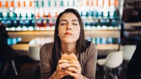 Ung kvinna som äter den fettiga hamburgaren Begärsnabbmat Tycka om skyldigt nöje som äter skräpmat Tillfredsställt uttryck avbrot royaltyfria bilder