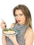 Ung kvinna som äter den tjuvjagad laxen och sallad Fotografering för Bildbyråer