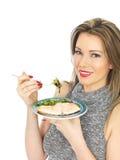Ung kvinna som äter den tjuvjagad laxen och sallad Royaltyfri Fotografi