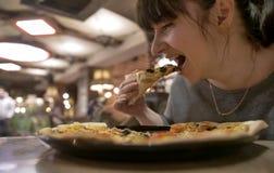 Ung kvinna som äter en skiva av pizza som sitter i ett kafé, closeup royaltyfria foton
