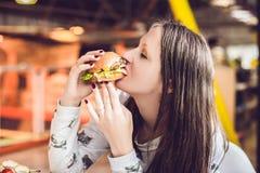 Ung kvinna som äter hamburgarekvinnan som äter skräpmat, fettig mat arkivbilder