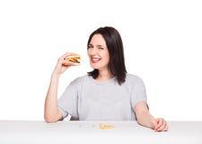 Ung kvinna som äter hamburgaren som isoleras på vit royaltyfri bild