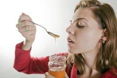 Ung kvinna som äter honung Royaltyfria Bilder