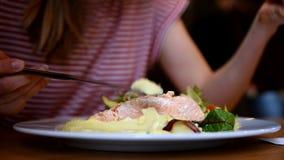 Ung kvinna som äter laxen i restaurang stock video
