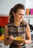 Ung kvinna som äter pumpasoppa i kök Arkivfoto