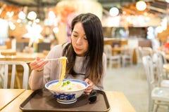 Ung kvinna som äter ramen i restaurang arkivfoto