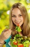 Ung kvinna som äter sallad Fotografering för Bildbyråer