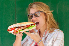 Ung kvinna som äter smörgåsen royaltyfri fotografi