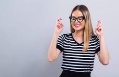 Ung kvinna som önskar för bra lycka fotografering för bildbyråer