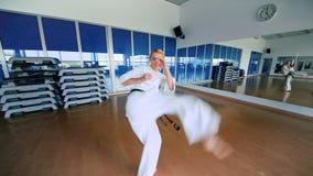 Ung kvinna som öva karatet i idrottshallen för sport` s lager videofilmer